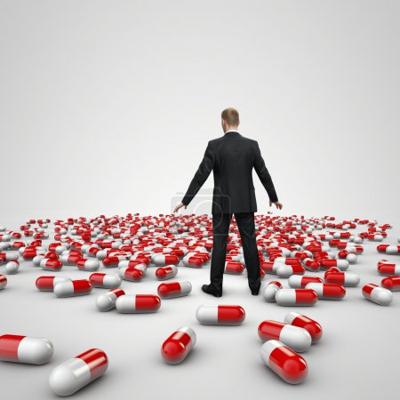 businessman figure standing in front of heap of red pills
