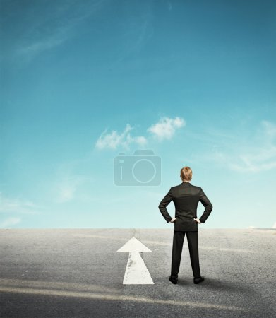 Background with businessman looking forward in desert and arrow
