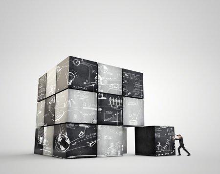 Photo pour Les cubes d'image géométrique. Homme d'affaires déplace un poids énorme - image libre de droit