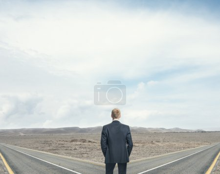 Businessman in front of two roads