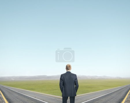 Photo for Businessman standing in front of two roads - Royalty Free Image