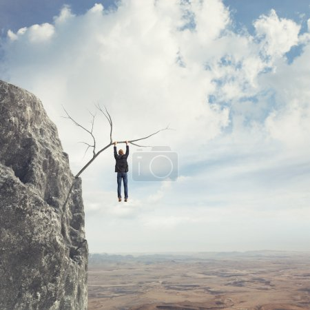 Business man climbs a mountain...