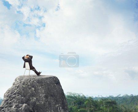 Photo pour Homme d'affaires assis sur un pic - image libre de droit