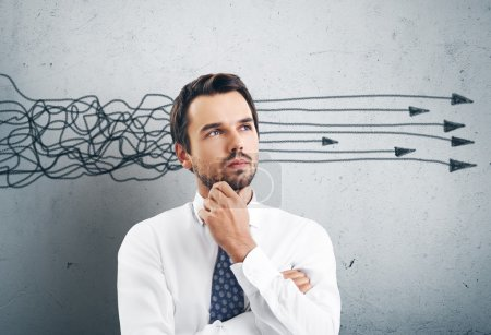 Photo for Young businessman has an idea. Thinking with arrows overhead - Royalty Free Image
