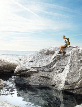 Traveler woman sitting on a rock near sea