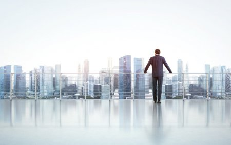 Photo for Businessman standing on a roof and looking at city - Royalty Free Image