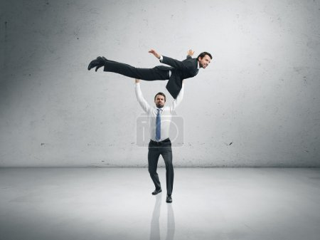 One businessman lifting the second one