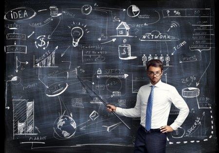 Foto de Hombre con puntero en la mano presentando estrategia de negocio - Imagen libre de derechos