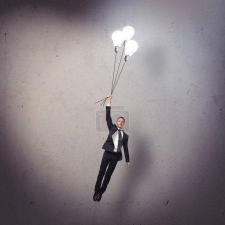 Businessman flying with light bulbs