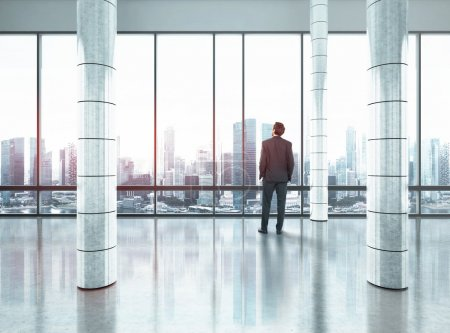 Businessman standing in large office and looking at city