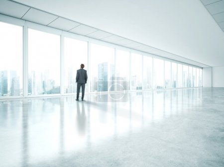 Photo for Businessman standing in empty bright office and look at city - Royalty Free Image