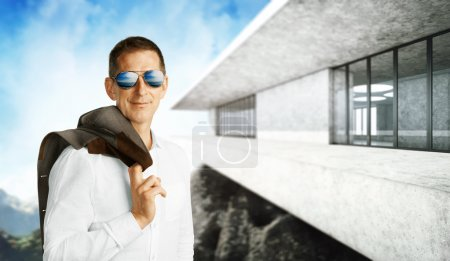 Photo for Businessman standing at office building on mountains background - Royalty Free Image