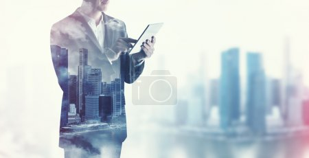 Photo for Double exposure of city and businessman using digital tablet - Royalty Free Image