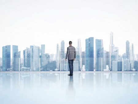 Photo for Businessman standing on a roof and looking city - Royalty Free Image
