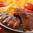 Barbecued pork baby back ribs against a hardwood f...
