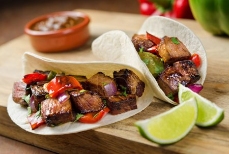 Photo for Two beef fajitas with red onion, peppers, cilantro, and lime. - Royalty Free Image