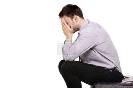Business man sat in despair isolated on a white background