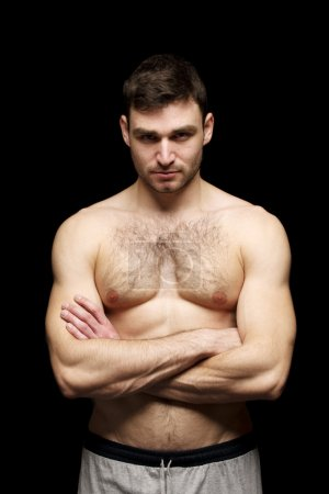 Photo for Topless man stood with his arms folded isolated on a black background - Royalty Free Image