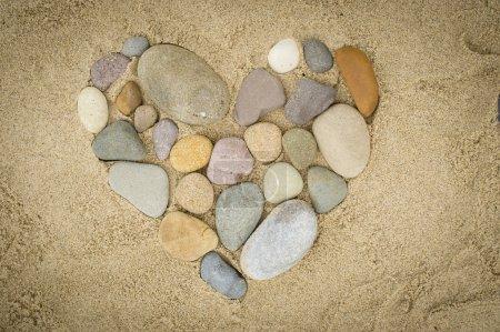 Photo pour Galets disposés en forme de cœur sur une plage de sable - image libre de droit