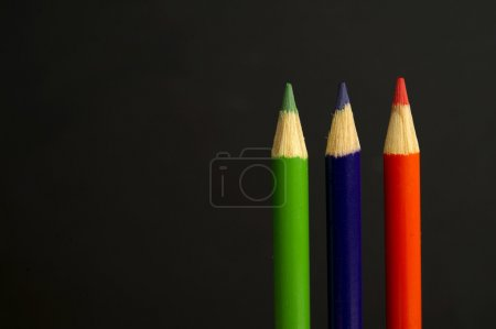 green, purple and orange coloured pencil crayons on a black back