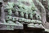 Lichen-covered carvings near Angkor Wat in Siem Reap, Cambodia