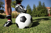 man standing with foot on soccerball