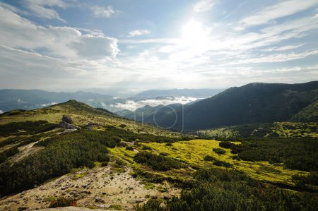 Foto de Hermoso paisaje de montaña. Las montañas son visibles al horizonte. Cielo nublado con el sol. Hay una niebla en el valle. Las colinas cubiertas de hierba y bosque. Nadie está por aquí. . - Imagen libre de derechos