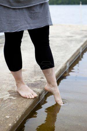 Photo pour Femelle tremper ses pieds dans l'eau. - image libre de droit