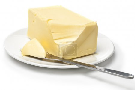 Piece of butter on white plate with knife. White b...