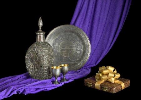 Photo pour La vaisselle argentée est sur le tissu violet drapé et le cadeau à côté. Fond noir . - image libre de droit