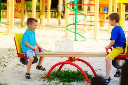 Foto de Niños jugando en el jardín en los columpios - Imagen libre de derechos