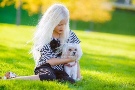 blond girl hugging a dog