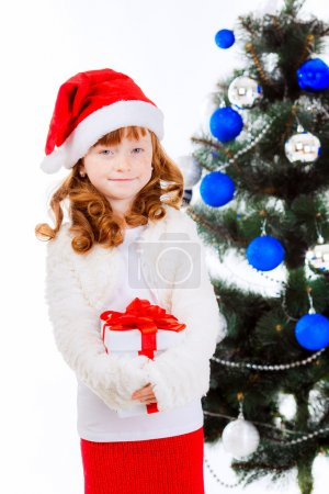 Little girl with gift near the Christmas tree