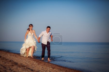 Couple running on the beach on their wedding day.