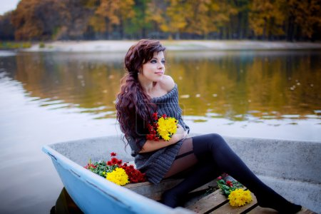 Beautiful girl in the boat with flowers.