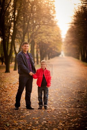 Photo for Dad and son handshake at the autumn park. - Royalty Free Image
