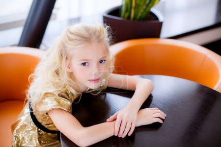 Photo for Fashion portrait of a little blond girl sitting at the table - Royalty Free Image