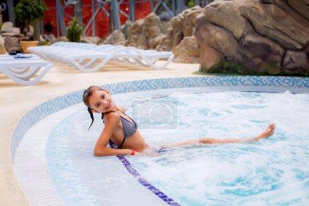 Photo pour Fille dans le jacuzzi dans le parc aquatique - image libre de droit