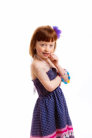 Little red-haired girl in a blue dress