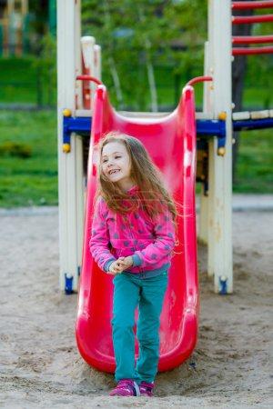 Photo for Lovely little girl on a children's slide - Royalty Free Image