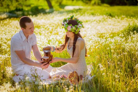 Couple relaxing on the meadow with dandelions on picnic