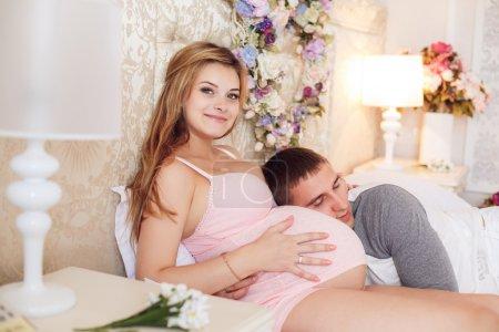 Photo pour Homme couché sur le ventre de femme enceinte sur le lit dans la chambre à coucher - image libre de droit