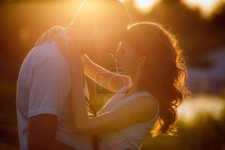 Photo pour Heureux mariés au coucher du soleil - image libre de droit