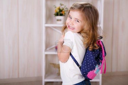 Little girl with a backpack in the room