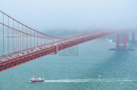 Closeup view of Golden Gate Bridge from Marin Headlands with a boat passing underneath in San Francisco, California