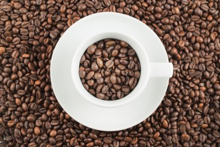 Photo for White ceramic plate with cup full of roasted coffee beans as a background composition, top view - Royalty Free Image