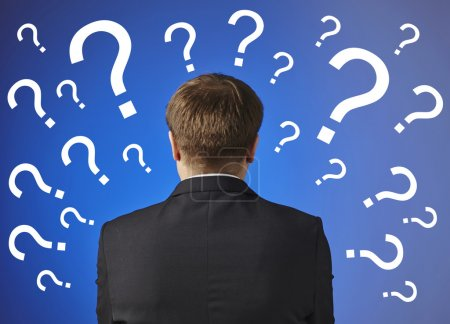 Businessman looking at   drawn question marks