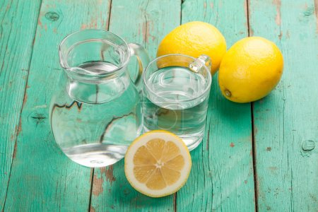 Glass and jar  with water and lemons