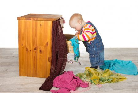 Photo for Happy baby standing searching in a drawer of a small wooden chest of drawers unpacking colourful clothes and textiles onto the floor in a random pile - Royalty Free Image