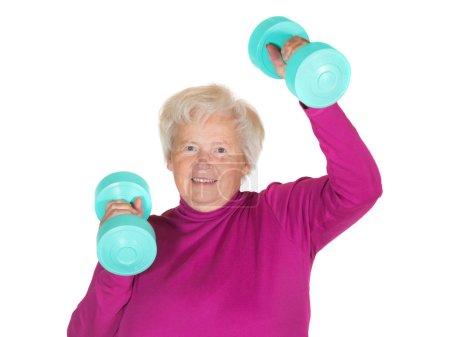 Photo pour Femme âgée enthousiaste travaillant avec des poids pour maintenir sa vitalité et son zeste pour la vie dans sa retraite - image libre de droit